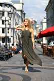 Beautiful young blonde woman in long dress. Portrait in full growth, attractive young blonde woman in long dress walking in summer street Stock Images