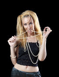 Beautiful young blonde woman with long hair and a pearl beads Royalty Free Stock Image
