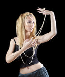 Beautiful young blonde woman with long hair and a pearl beads on dark background. Royalty Free Stock Images