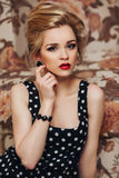 Beautiful young blonde woman with long hair in a. Portrait of a beautiful young blonde woman with long hair in a retro polka-dot dress Royalty Free Stock Image