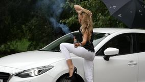 Beautiful young blonde woman standing near white car. Gorgeous girl poses with smoke. slow motion stock footage