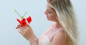 Beautiful young blonde woman looking at flowers stock video