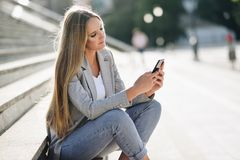 Beautiful young blonde woman looking at her smartphone. Stock Photos