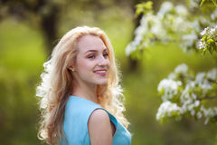 Beautiful young blonde woman looks around, smiling.Portrait of a girl in a flowered garden Royalty Free Stock Photos