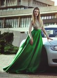 A beautiful young blond woman in a luxurious green evening dress near car. royalty free stock image