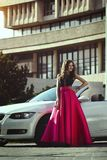 A beautiful young blonde woman in a luxurious pink long evening dress is standing near a cabriolet car. Royalty Free Stock Photos