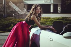 A beautiful young blonde woman in a luxurious pink long evening dress is standing near a cabriolet car. Stock Photos