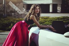A beautiful young blonde woman in a luxurious pink long evening dress is standing near a cabriolet car. Royalty Free Stock Images