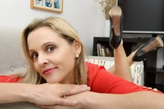 Beautiful young blonde woman lying on the couch Royalty Free Stock Image