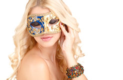 Beautiful young blonde woman in a mysterious Venetian mask. Stock Image