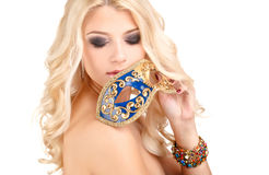 Beautiful young blonde woman in a mysterious Venetian mask. Stock Photo