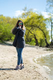 Beautiful young blonde woman outdoor on the lake shore, is thoughtful, warm filter is applied, the wind in your hair. Royalty Free Stock Photography