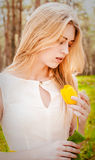 Beautiful young blonde woman. Outdoor with a tulip Royalty Free Stock Photos