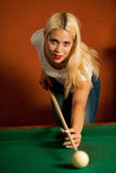 Beautiful young blonde woman playing billiard in a bar Stock Image