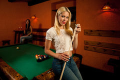 Beautiful young blonde woman playing billiard in a bar Royalty Free Stock Photo