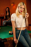 Beautiful young blonde woman playing billiard in a bar Stock Photography