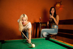 Beautiful young blonde woman playing billiard in a bar Stock Images