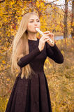 Beautiful young blonde woman playing flute recorder in autumn forest Stock Photos