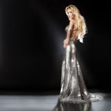 Fashion picture of beautiful young blonde woman wearing glitter. Beautiful young blonde woman posing in fashionable silver evening dress on the scene. Long curly Stock Photos
