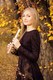 Beautiful young blonde woman posing with flute recorder in autumn forest Royalty Free Stock Photos