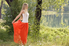 Beautiful young blonde woman posing in forest near riverbank Stock Photos