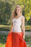 Beautiful young blonde woman posing in forest near riverbank Royalty Free Stock Images