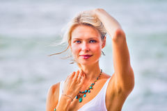 Beautiful young blonde woman posing outdoor at the rocky sea sho Stock Image
