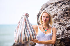 Beautiful young blonde woman posing outdoor at the rocky sea sho Stock Photos