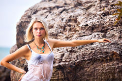 Beautiful young blonde woman posing outdoor at the rocky sea sho Royalty Free Stock Photo
