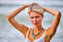 Beautiful young blonde woman posing outdoor at the rocky sea sho Royalty Free Stock Images