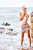 Beautiful young blonde woman posing outdoor at the rocky sea sho Stock Images