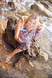 Beautiful young blonde woman posing outdoor at the rocky sea sho Royalty Free Stock Photography