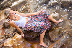 Beautiful young blonde woman posing outdoor at the rocky sea sho Royalty Free Stock Image