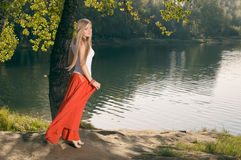 Beautiful young blonde woman posing under the tree on riverbank Royalty Free Stock Images