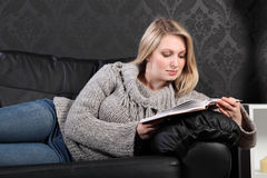 Beautiful young blonde woman reading book at home Royalty Free Stock Images
