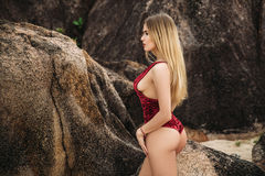 Beautiful young blonde woman in red bikini posing on the beach. Sexy model portrait with perfect body. Concept of summer Stock Photo