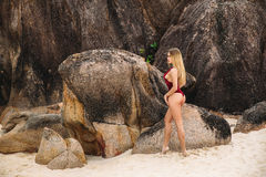Beautiful young blonde woman in red bikini posing on the beach. Sexy model portrait with perfect body. Concept of summer Stock Photography