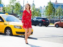 Beautiful young blonde woman in red dress. Walking on the summer street royalty free stock images