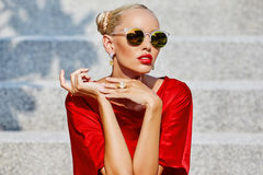 Beautiful young blonde woman in red dress and sunglasses outdoor Stock Photo