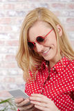 Beautiful young blonde woman with red shirt and phone Stock Photos