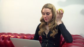 Beautiful young blonde woman on red sofa using laptop and eating a green apple in living room. Slider shot 4k stock footage
