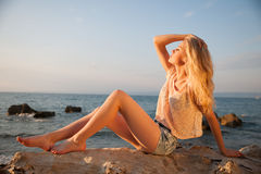 Beautiful young blonde woman resting on a beach at dusk in early Stock Image
