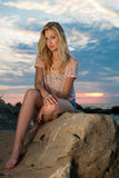 Beautiful young blonde woman resting on a beach at dusk in early Royalty Free Stock Photography
