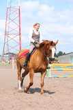 Beautiful young blonde woman riding chestnut horse Royalty Free Stock Photo
