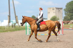 Beautiful young blonde woman riding chestnut horse Royalty Free Stock Photos