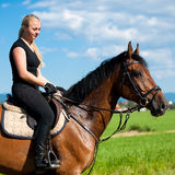 Beautiful young blonde woman riding a horse. On a farm Royalty Free Stock Photo