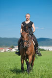 Beautiful young blonde woman riding a horse. On a farm Royalty Free Stock Images