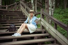 Beautiful young blonde woman sits on wooden steps in a city park with a book in hands. She is wearing a white dress, a Royalty Free Stock Photography