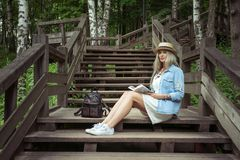 Beautiful young blonde woman sits on wooden steps in a city park with a book in hands. She is wearing a white dress, a Stock Image