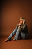 Beautiful young blonde woman sitting barefoot Stock Images